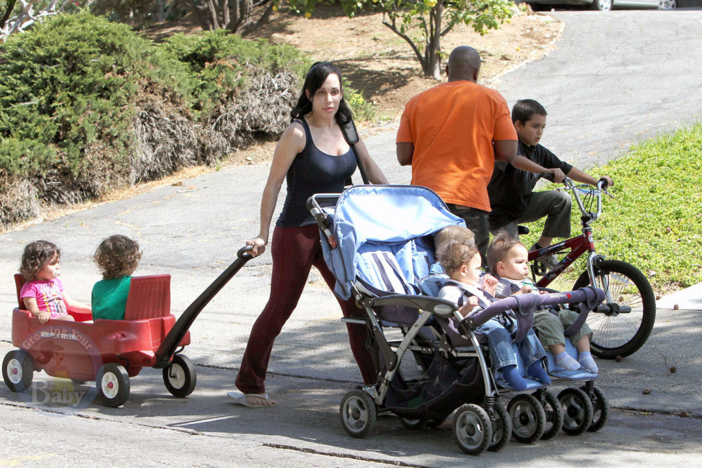 Nadya Suleman pushes and pulls her kids after having some fun at the park despite facing foreclosure on her family home